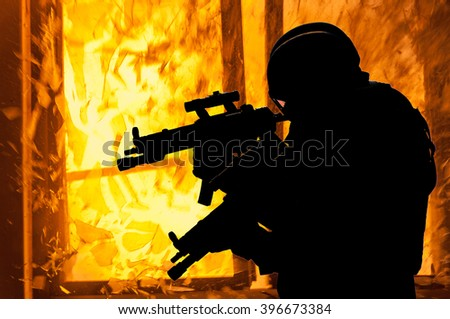 Special weapons and tactics team (SWAT) officers silhouette in the explosion - stock photo