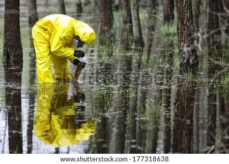 specialist in coveralls taking sample of water to container in floods contaminated area - stock photo