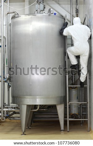 Specialist in white uniform climbing a ladder on industrial tank in factory - stock photo