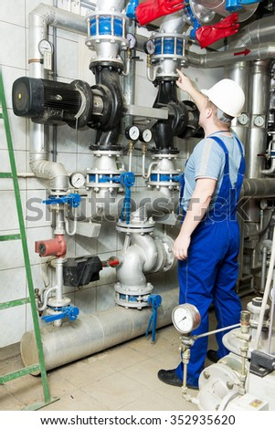 specialist looks at the pumps and pipes - stock photo