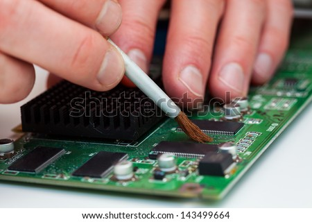 Specialist use brush to clean dusty microchip - stock photo