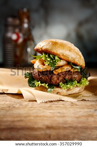 Speciality seafood and beef burger with grilled prawns and a juicy beef patty on lettuce served on a rustic counter for a pub lunch - stock photo