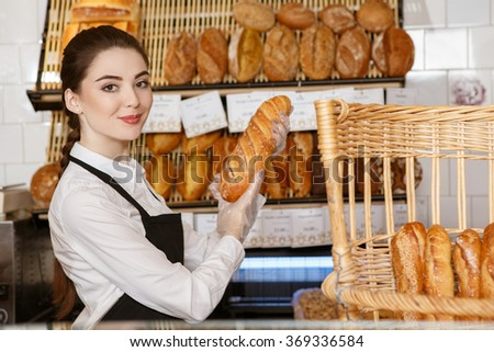 Specially for you. Portrait of a female baker holding out freshly baked bread smiling joyfully to the camera  - stock photo