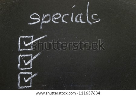 specials title handwritten with white chalk on blackboard, copy space below, restaurant advertisement - stock photo