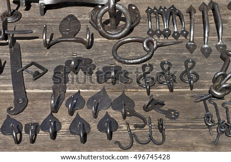 Specimens of rustic ironwork on wooden table.