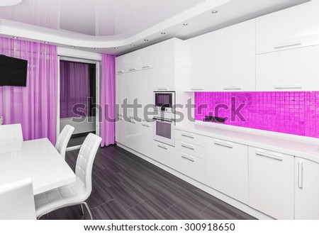 Specious modern white pink interior kitchen-dining room with the built-in household appliances and the TV - stock photo