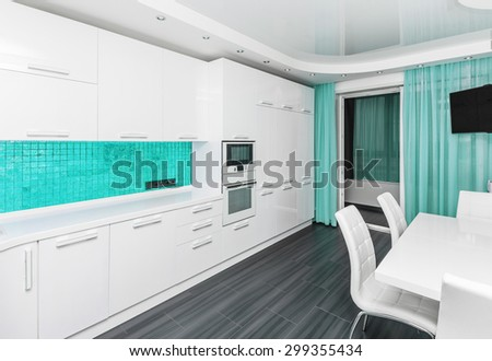 Specious modern white  turquoise interior kitchen-dining room with the built-in household appliances and the TV - stock photo