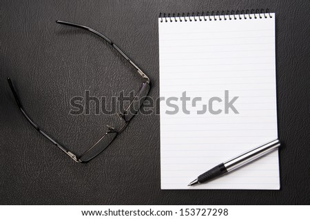 Spectacles and writing pad with lots of copy space - stock photo