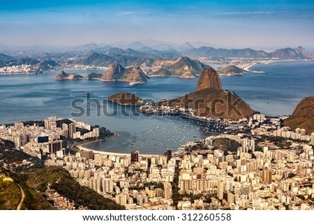 Spectacular aerial view over Rio de Janeiro as viewed from Corcovado. The famous Sugar Loaf mountain sticks out of Guanabara Bay - stock photo