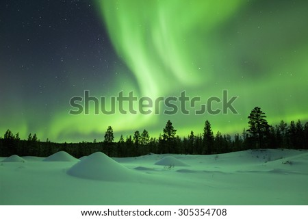 Spectacular aurora borealis (northern lights) over a snowy winter landscape in Finnish Lapland. - stock photo