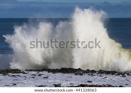 Spectacular backwash from the  Indian Ocean waves breaking on basalt rocks at  Ocean beach Bunbury Western Australia on a sunny morning in early winter  sends salty spray high into the air.