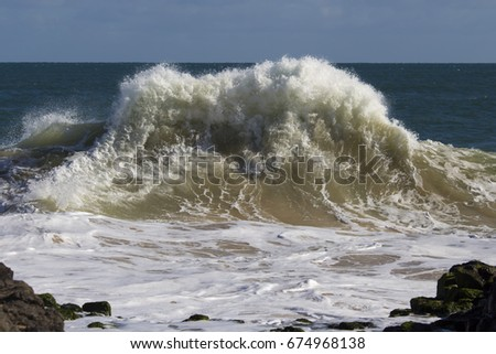 Spectacular backwash from the  Indian Ocean waves breaking on basalt rocks at  Ocean Beach Bunbury Western Australia on a sunny morning in mid-winter  sends salty spray high into the air.