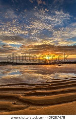 spectacular beach reflection at sunrise on the scenic Hawaiian island of Kauai - stock photo