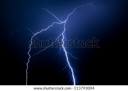 Spectacular blue lightning strike in the night with no buildings or trees - stock photo