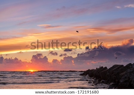 Spectacular colorful seascape of Baltic sea at sunset after storm with breakwater in foreground leading to sun at horizon - stock photo