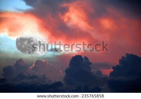 Spectacular fiery sunset with a splash of blue sky and the moon lurking between the clouds for background