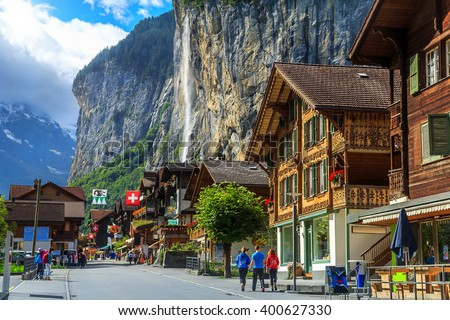 Spectacular principal street of Lauterbrunnen with shops,hotels,terraces,swiss flags and stunning Staubbach waterfall in background,Bernese Oberland,Switzerland,Europe - stock photo