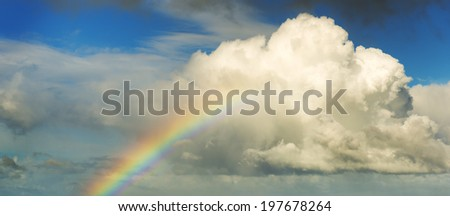 Spectacular rainbow in bright colors rising up to a huge white cloud with blue sky - stock photo