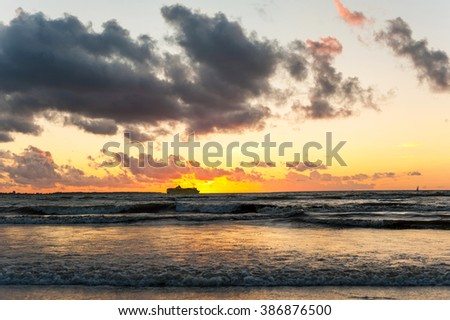 Spectacular summertime sunset on Baltic sea with cruise ferry ship silhouette. Colorful dramatic Blue sky background. Horizontal outdoors image - stock photo