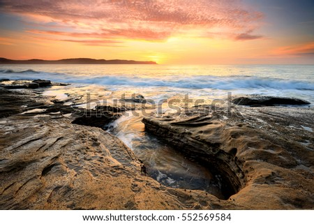 Spectacular sunrise beautiful skies and light from the rocky coastline near Pearl Beach, Australia