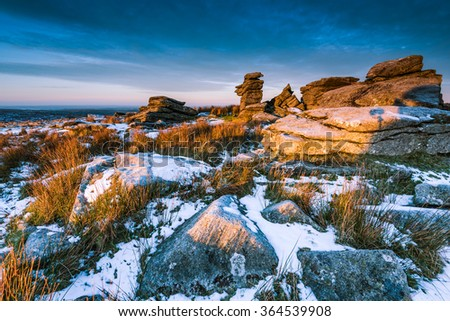 Spectacular sunrise on rocky hill mountain at snowy morning in Dartmoor National Park, Devon,UK. - stock photo