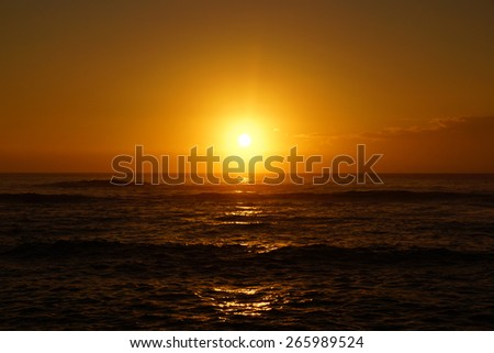 Spectacular Sunrise over the ocean with waves rolling toward shore in Hana on Maui, Hawaii.    - stock photo