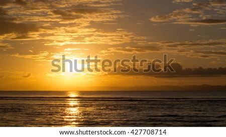 Spectacular sunset over calm ocean water, Ile aux Nattes, Madagascar - stock photo