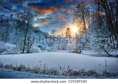 Spectacular sunset over winter forest lake  - stock photo