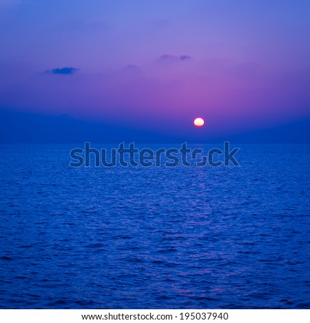 Spectacular sunset. Setting sun painted the sky, clouds and ocean in Deep blue color. - stock photo