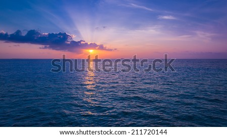 Spectacular sunset. Setting sun painted the sky, clouds and ocean in deep  colors. - stock photo