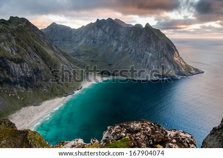 Spectacular sunset view to rugged mountain peaks above Kvalvika - famous surfing beach at Lofoten islands, Norway - stock photo