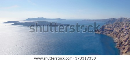 Spectacular view from the coastline of the Island Santorini and his volcanic caldera  with  little islands in the distance - stock photo