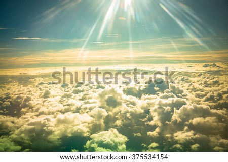 Spectacular view of a sunset above the clouds from airplane window. - stock photo