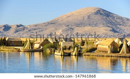 Spectacular view of the Uros island and the boats with the reflection on the lake Titicaca, Peru - stock photo