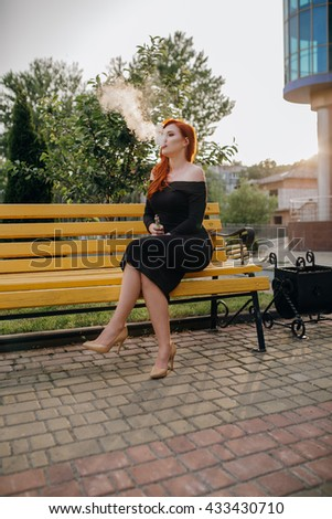 spectacular young orange-brown outside uses fashionable and healthy e-cigarette