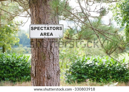 spectator viewing area sign on a pine tree - stock photo