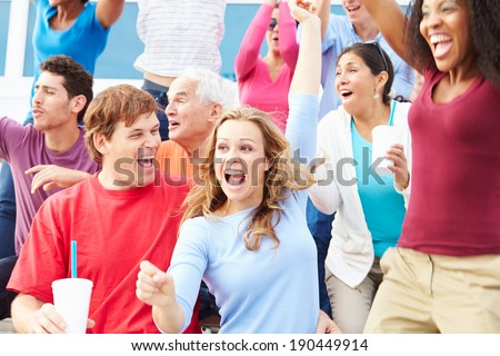 Spectators Celebrating At Outdoor Sports Event - stock photo