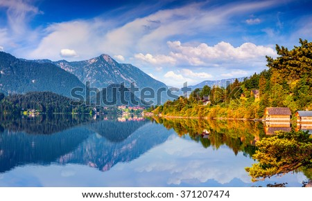 Specular reflection at the water surface of blue mountain in Grundlsee lake. Archkogl village in the morning mist. Bezirk Liezen district of Styria in Austria, Alps, Europe.