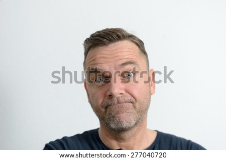 Speechless middle-aged unshaven man looking at camera with blue eyes and perplexed facial expression, portrait with copy space on gray - stock photo