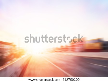 Speed blur expressway asphalt road with car in a city landscape at sunrise. Driving on a Highway with colorful sky. Blurred of peaceful landscape sunset. Abstract blur glowing bokeh colorful. - stock photo