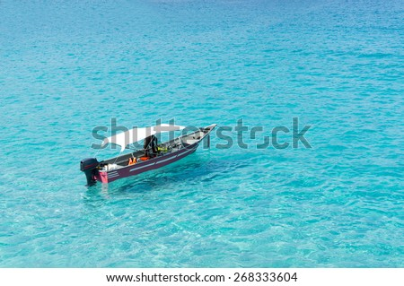 speed boat floating on crystal clear water - stock photo