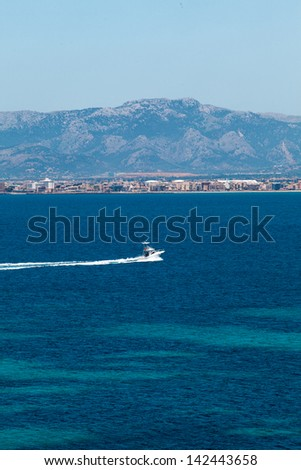 Speed boat in a quiet bay with beach. Majorca island, Spain