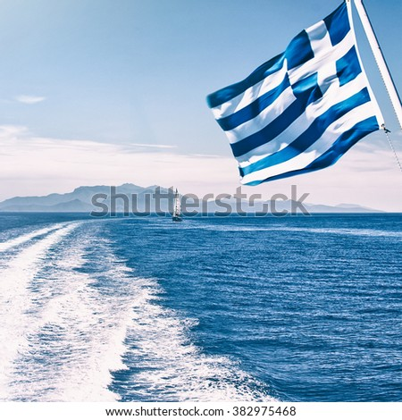 Speed boat traces on water in the Aegean sea little boat and flag of Greece in motion. Europe