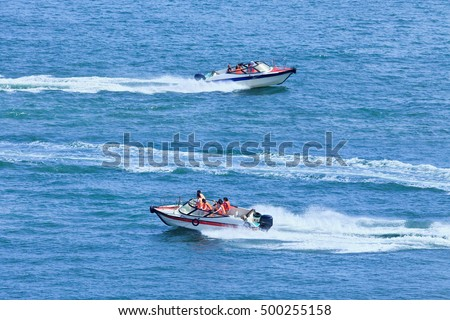 Speed boats passing each other in a blue sea