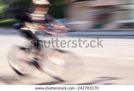 Speed. Boy cyclist in traffic on the city roadway. Intentional motion blur - stock photo