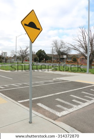 speed bump on asphalt road with yellow and black sign - stock photo