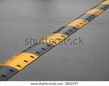 speed bump on wet road - stock photo