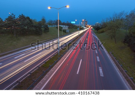 Speed drive on freeway at the entrance to Belgrade, Serbia with a view to the West Towers in the background. Light trails at rush hour on motorway in long exposure shot. - stock photo