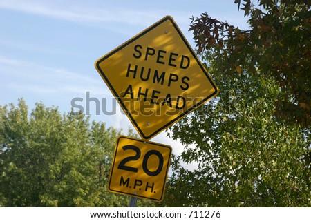 Speed hump sign under tree - stock photo