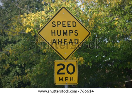 Speed humps sign with trees - stock photo